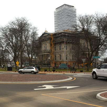 Cars progress through the roundabout at the corner
