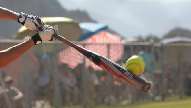 A softball player connects with a pitch.