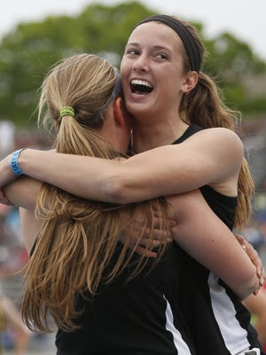 Pleasant Valley's Carly Donahue hugs teammate Kelli DeGeorge Saturday, May 23, 2015 as they take the win in the girls 4-A shuttle hurdle relay at the state track meet in Des Moines.