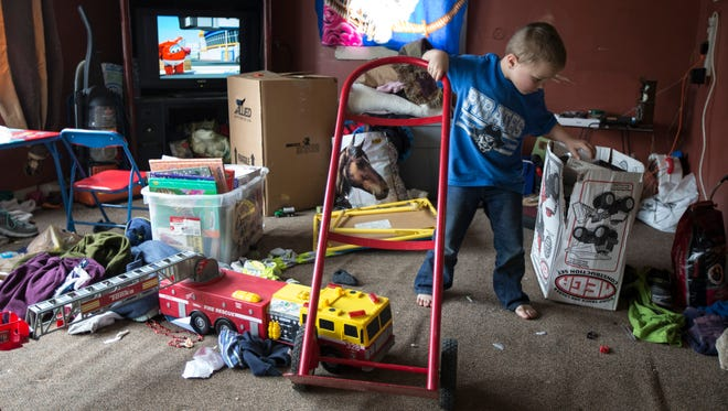 Michael Parrish, Jr. pretends to load up and move his toys while his family loads up their belongings from their Pleasant Ridge home Friday. March 24, 2017