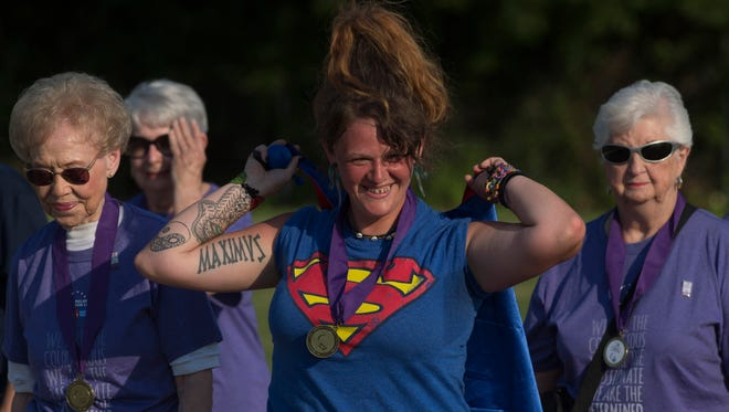 Cancer survivor Heather Smith, center, adjusts her Supergirl cape during the survivors walk at the Relay for Life event at North Middle School Friday evening.