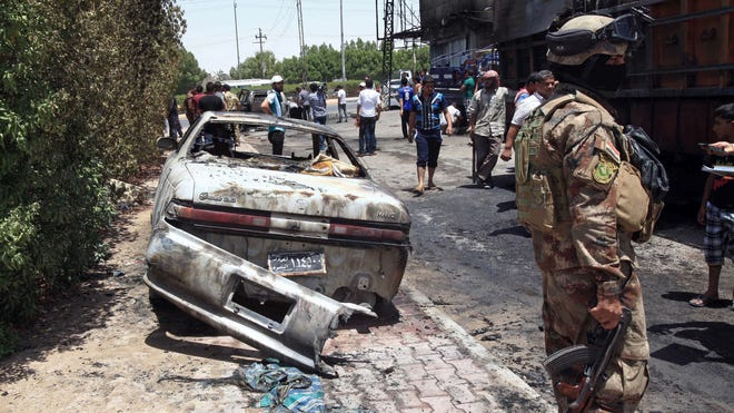 Iraqi security forces inspect the site of a bomb explosion near Baghdad in July.