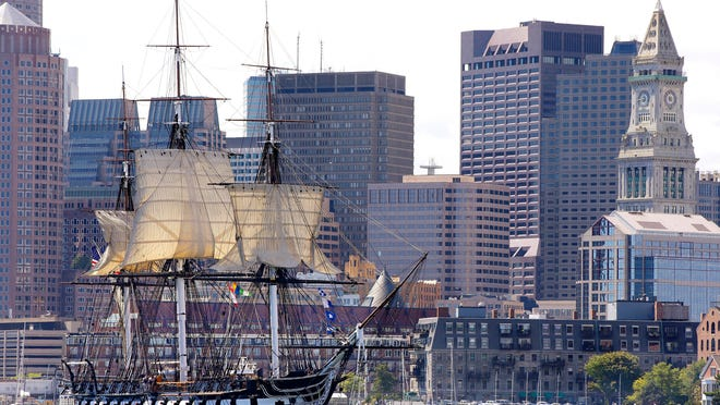 """The USS Constitution, nicknamed """"Old Ironsides,"""" the U.S. Navy's oldest commissioned ship that is still afloat, is towed through Boston Harbor past Boston's financial district skyline with its topsails unfurled. The warship officially closed Monday, April 27, and will partly reopen June 9, before entering dry dock near its berth on May 19 for a multi-year restoration project."""