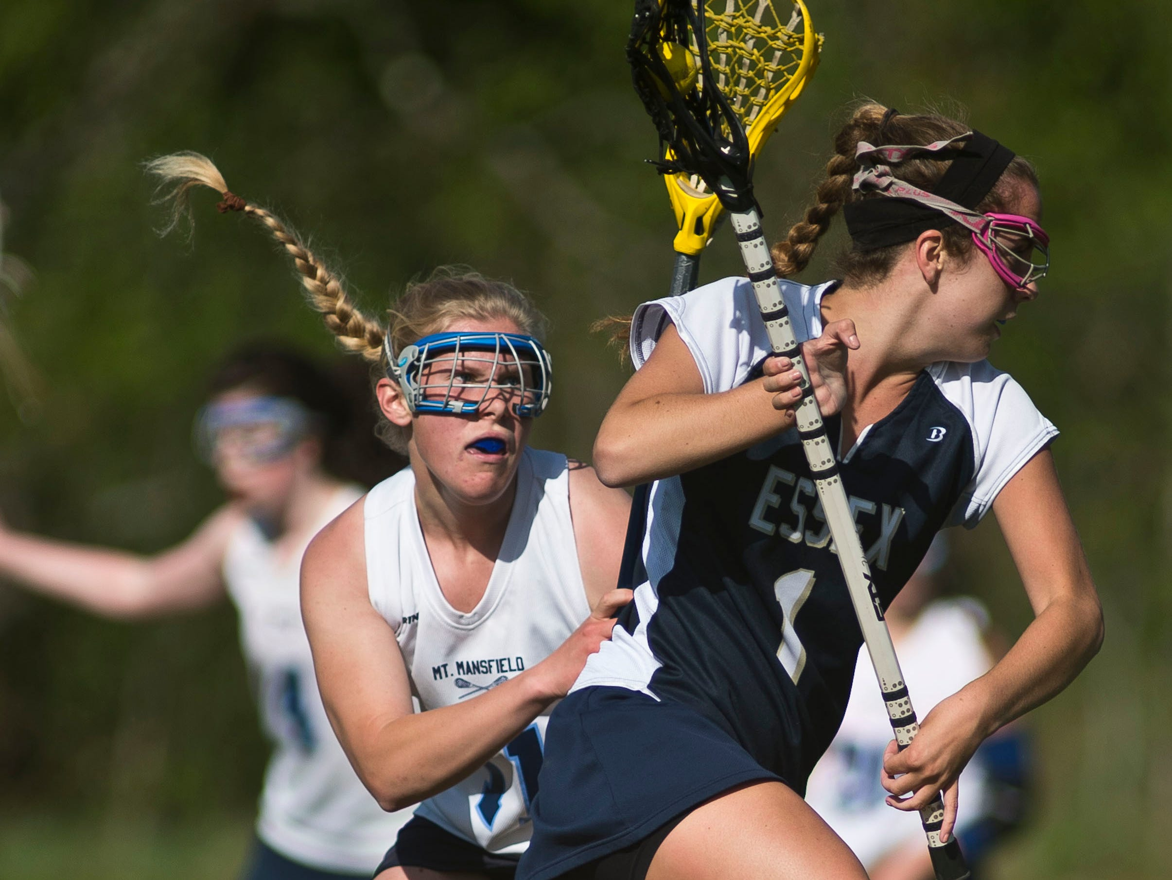 Essex's Olivia Malle (1) gets around Mount Mansfield's Karin Rand during their girls lacrosse game in in Jericho earlier this month.