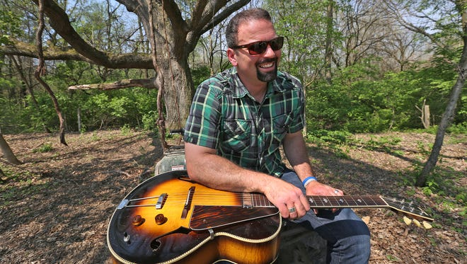 Former Indianapolis Colts punter Hunter Smith shows the guitar his grandfather gave him before singing one of his new songs Thursday, May 7, 2015.  He has traded in football   for music and is set to release a new album.