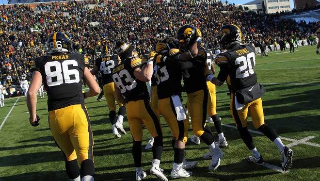 Iowa teammates celebrate the Hawkeyes' 40-20 win over Purdue at Kinnick Stadium on Saturday. The victory clinched the Big Ten West Division title, later earned outright with Wisconsin's loss to Northwestern.