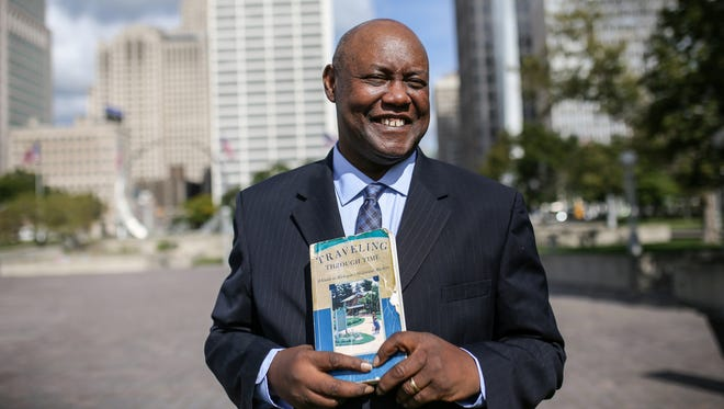 Cliff Russell, a local journalist and radio personality,  has visited 1,200 of Michigan's 1,800 historical markers and is photographed at one of them, The Landing of Cadillac, in Hart Plaza in downtown Detroit on Thursday, Sept. 7, 2017. Russell read about this markers in Laura Ashley's book Traveling Through Time that he holds in his hands.