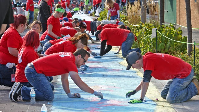 Eli Lilly employees join in on the artistic work on Virginia Ave. as part of an attempt to break the Guinness World Record of the largest display of chalk pavement art, Thursday, Sept. 28, 2017.