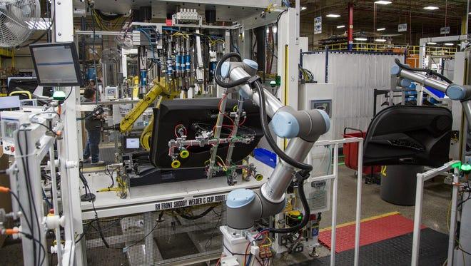 Collaborative robots help assemble a Chevrolet Cruz door at the IAC plant in Huron, Ohio, on Thursday, October 19, 2017.