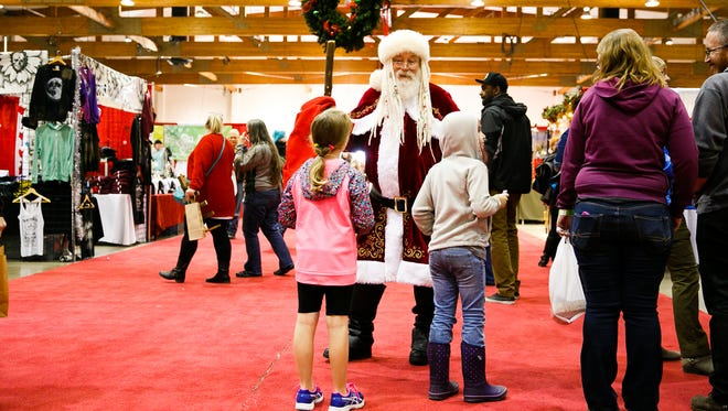 Santa Claus talks to children at the 2017 Salem Holiday Market at the Oregon State Fairgrounds.