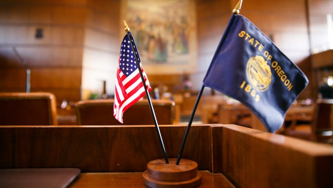 An American flag and the flag of Oregon on a legislator's desk before a naturalization ceremony for new citizens on Wednesday, Feb. 14, 2018, in the Senate Chamber at the Oregon State Capitol. Thirteen immigrants from six countries were naturalized during the ceremony, held on Oregon's 159th birthday.