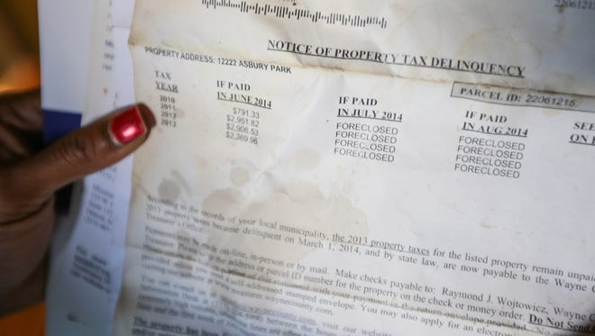Marcella Crockett of Detroit holds a letter from the Wayne County Treasurer showing the back taxes she owes on her home in Detroit on September 10, 2014.