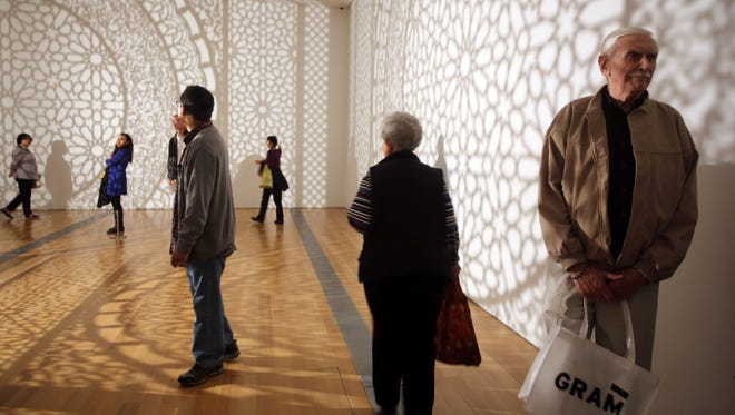 "People take in the 3-D piece of Anila Quayyum Agha's ""Intersections"" at the Grand Rapids Art Museum."