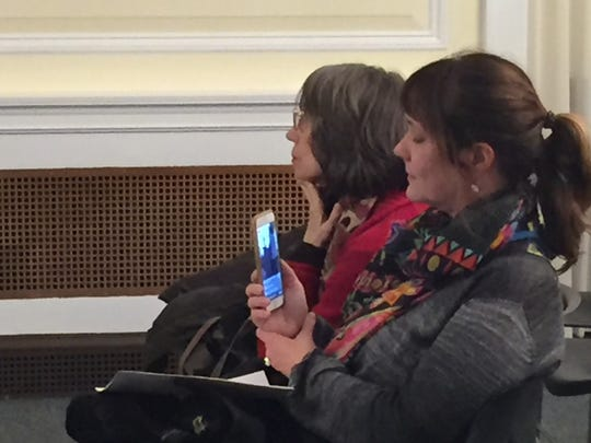"""Yvonne Gumowitz uses her cell phone to post live video of """"Citizens to be Heard"""" on Facebook."""