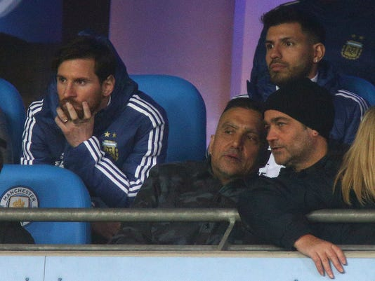 Argentina's Lionel Messi, left, and Sergio Aguero, top right, sit on the bench before the international friendly soccer match between Argentina and Italy at the Etihad Stadium in Manchester, England, Friday, March 23, 2018. (AP Photo/Dave Thompson)