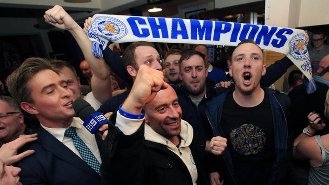 Leicester City fans celebrate in the Market Tavern in Leicester after seeing their side crowned English Premier League soccer champions following Tottenham Hotspur's 2-2 draw against Chelsea. The match resulted in Leicester City winning the Premier League, Monday May 2, 2016. (Jonathan Brady/PA via AP) UNITED KINGDOM OUT NO SALES NO ARCHIVE