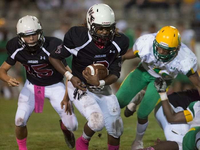 West Florida High School's Marquis Ross, (No.3) breaks through the Catholic High School defensive line and turns up field during Friday night's games against the crusaders.