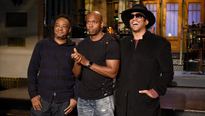 Jarobi White and Q-Tip of musical guest A Tribe Called Quest pose with host Dave Chappelle (center) on November 10, 2016.