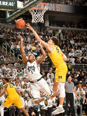 Michigan State's Cassius Winston scores off the glass with a shot that gets past Michigan's D.J. Wilson.