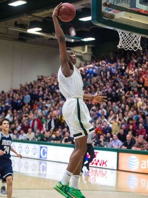 Rice's Kendrick Gray dunks the ball in the final moments against Burlington during the D-1 boys state basketball championship at Patrick Gymnasium in Burlington on Saturday, March 7, 2015.