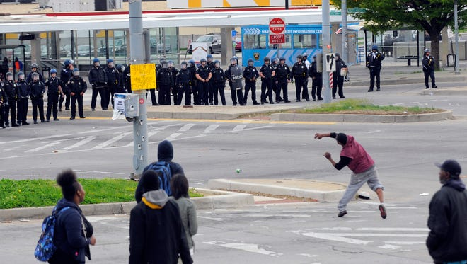 Protestors toss objects at members of the Baltimore Police Department, Monday, April 27, 2015, during unrest following the funeral of Freddie Gray in Baltimore. Rioters plunged part of Baltimore, torching a pharmacy, setting police cars ablaze and throwing bricks at officers.