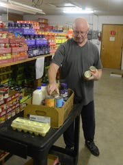 Larry Faist packs a box of food for a family while