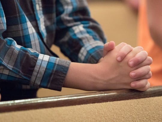 Mikah Bruner prays during Vacation Bible School Tuesday