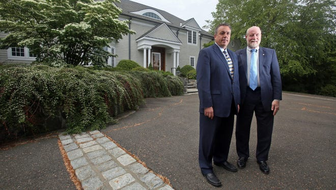 Daniel Luckner and Nicholas Wolff, realtors with Better Homes & Garden Rand Realty, photographed outside 535 Polly Park Drive in Harrison June 4, 2015. The home borders the grounds of Westchester Country Club, with the backyard separated from one of the golf course fairways by shrubs and a wooden fence.
