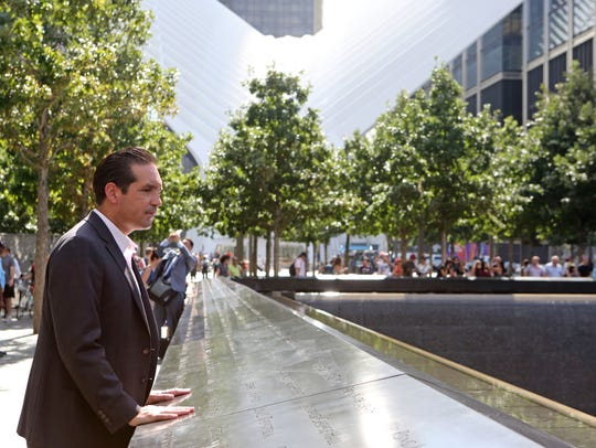 Glenn Guzi stands at the site's north reflecting pool,