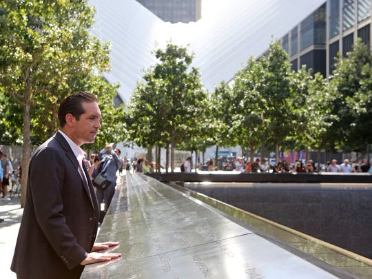 Glenn Guzi stands at the site's north reflecting pool, where Port Authority employees are memorialized.