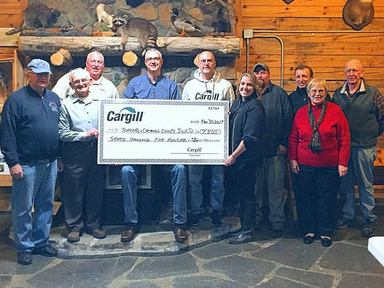 Representatives from Cargill present a check to board