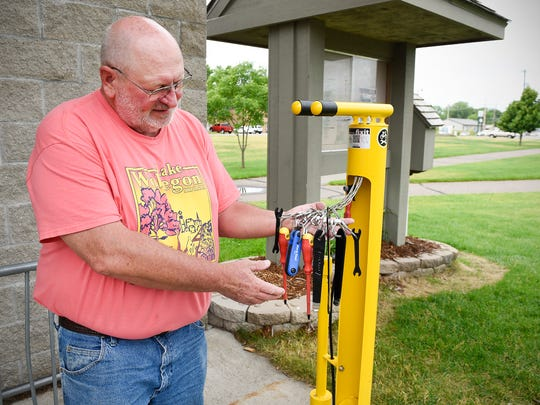 Cliff Borgerding, a member of the Lake Wobegon Trail Association board of directors, show the tools available at the new bike service station on the Lake Wobegon Trail Thursday, June 28, in Avon. There are seven service stations with basic bike tools and a tire pump located along the trail.