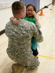 Kindergartener Bianca Withers cries with her father, U.S. Army Staff Sgt. Joshua Withers, during a surprise reunion on Friday morning at Thomas Jefferson Elementary School.
