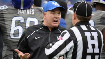 UK head coach Mark Stoops talks with an official during the University of Kentucky football game against University of Louisville at Commonwealth Stadium in Lexington, Ky., on Saturday, November 28, 2015.