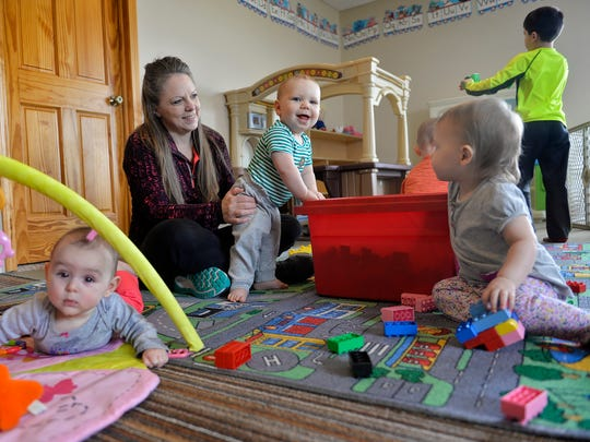 In-home child care provider Kelly Martini holds Abel Sand, 11 mos., as she plays with some of her charges Tuesday, March 29 at her Avon area home.