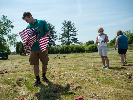 Joshua Wayne, left, of Abbottstown looks for a grave