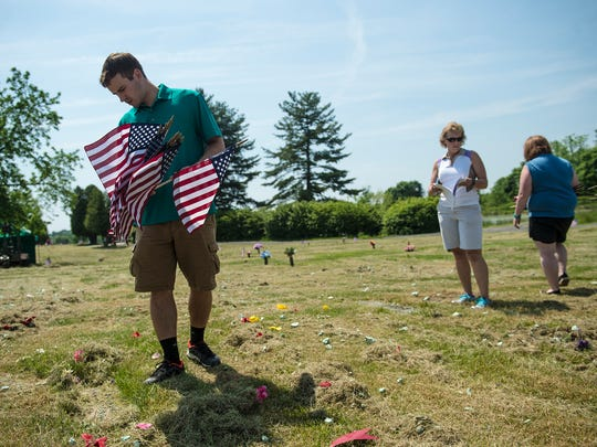 Joshua Wayne, left, of Abbottstown looks for a grave to set a flag on at Oak Lawn Memorial Gardens in Cumberland Township. Wayne is a summer intern with the Adams County Office of Planning and Development.