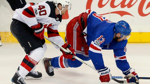 New York Rangers center Kevin Hayes (13) slips as he and New Jersey Devils center Blake Coleman (40) chase after the puck during the third period of an NHL hockey game game, Saturday, Oct. 14, 2017, in New York. The Devils won 3-2. (AP Photo/Julie Jacobson)