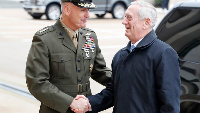 Chairman of the Joint Chiefs Gen. Joseph Dunford, left, shakes hands with Secretary of Defense James Mattis as Mattis arrives at the Pentagon, Jan. 21, 2017 in Washington.