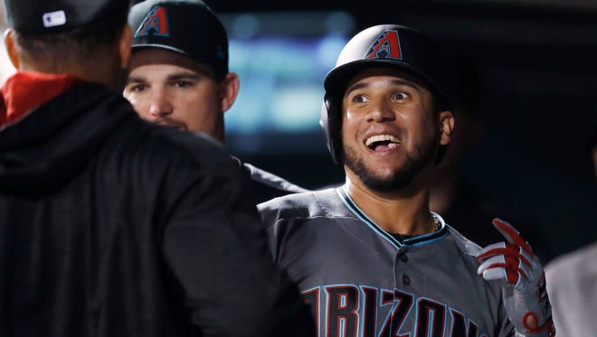 Arizona Diamondbacks' David Peralta, right, is congratulated by teammates as he returns to the dugout after hitting a solo home run off Colorado Rockies relief pitcher Chris Rusin to lead off the top of the eighth inning of a baseball game Tuesday, June 20, 2017, in Denver. Colorado won 4-3.