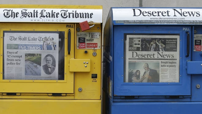 In this June 16, 2014, file photo, the Salt Lake Tribune and Deseret News newspaper boxes await customers in Salt Lake City. Democratic state Sen. Jim Dabakis says he is part of a group of five people who want to make a run at buying The Salt Lake Tribune.