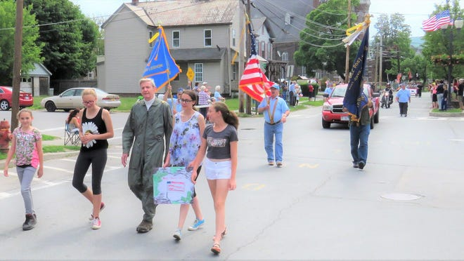 Retired Air Force Major Adrian Patrick Warnshuis marches with granddaughters Ashley Mills, Heather Mills, and Amber Carlton in a Memorial Day parade in Port Jervis.