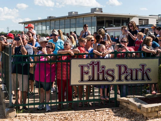 People gather along the fence to take pictures of jockeys and camels after a race at Ellis Park in Henderson, Ind., on Saturday, July 8, 2017.