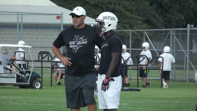 Green Bay West football coach Jeff Behrendt discusses an offensive play with senior running back Jamar Brown at practice Tuesday.