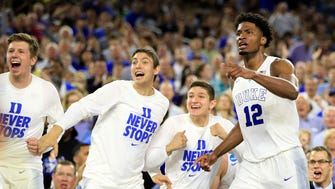 Duke Blue Devils forward Justise Winslow (12) and bench players celebrate after a basket against the Gonzaga Bulldogs during the second half in the finals of the south regional of the 2015 NCAA Tournament.