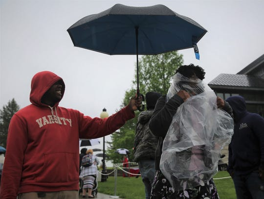 Roxanne Adams, right, puts on her poncho  as her son,