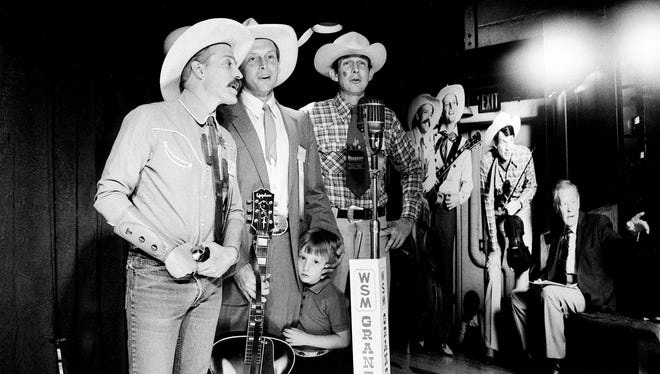 Western singing favorites Riders in the Sky try out a replica of the Grand Ole Opry stage in front of an enlarged photo of themselves backstage at the Opry during the exhibit opening April 29, 1986. Enjoying the moment are Fred ÒToo SlimÓ LaBour, Ranger Doug Green, with son Jamie, and Woody Paul.
