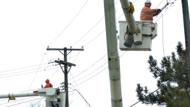 Workers repair power lines.