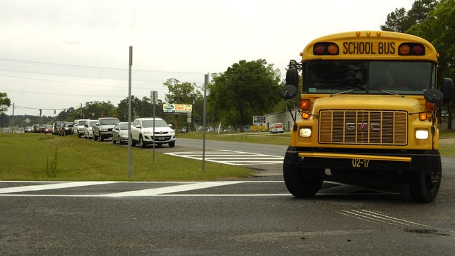 A school bus pulls into the Paradise Elementary School driveway in this photo from April 2014 while vehicles (left) are lined up on the shoulder of U.S. Highway 165 as drivers wait for school to let out so they can pick up children. Vehicles lining the highway create a dangerous situation, officials say, and a road project costing about $200,000 is in the works to resolve the problem.
