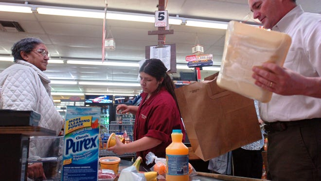 Breaux's Mart owner Karl Breaux bags groceries for shopper Regina Bernard as clerk Kandice Gaspard scans items Wednesday afternoon at the grocery store. By Leslie Westbrook March 27, 2008